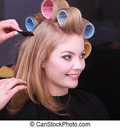 Blond girl hair curlers rollers by hairdresser in...