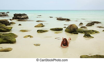attractive woman sunbathing in gorgeous crystal water,...