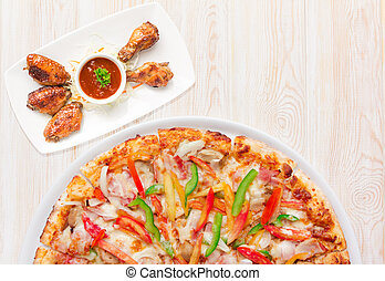 Delicious fresh pizza served with Chicken Wings