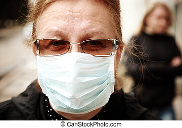 woman protecting herself against influenza with a face mask...
