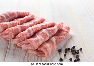 thin slices of fresh beef on wood background