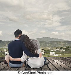 Asian young couple sit and hug together against the sky in...