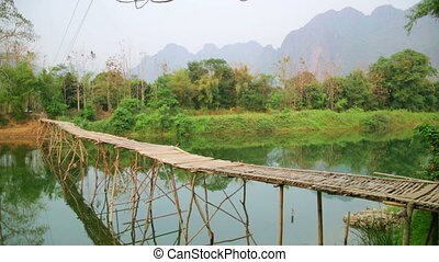 Majestic empty bamboo bridge, limestone mountains, vang...
