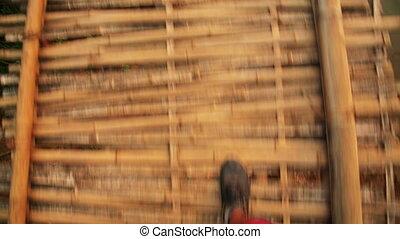 walking on dangerous bamboo bridge, laos