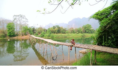Tourist girl sitting and drinking coffee on bamboo bridge,...