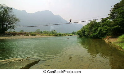 Tourist woman crossing dangerous bamboo suspension bridge,...