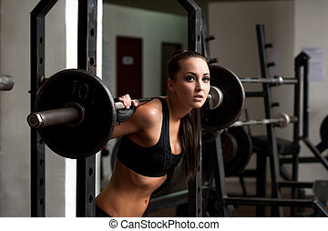 Beautiful brunette posing exercising with barbell -...