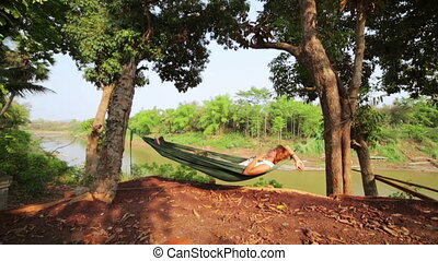 tourist girl sleeping on hammock, luang prabang, laos