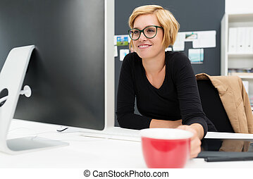 Businesswoman drinking coffee as she works holding a red cup...