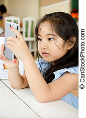 Happy Asian child  touching with smart phone