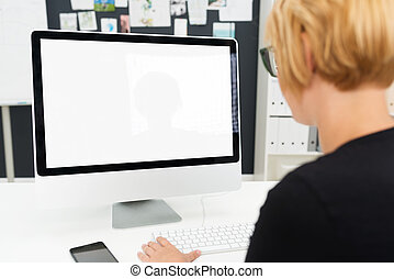Businesswoman working at a blank computer monitor - Over the...