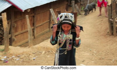 indigenous tribal native Akha woman carry water in bamboo stick