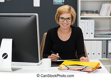 Smiling young woman working in an office - Smiling young...