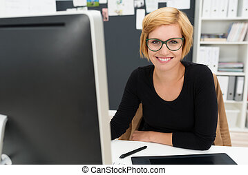 Friendly attractive young businesswoman sitting at her desk...