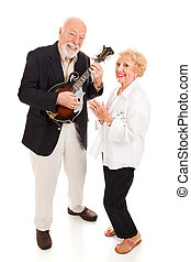 Senior Musicians - Senior man plays mandolin while his wife...