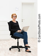 Young businesswoman lost in thought as she sits on an office...