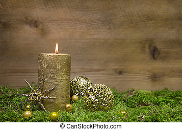 First advent: golden candle burning before wooden background...