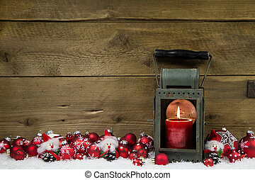 Wooden christmas background with red candle in a latern and...