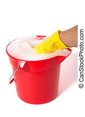 Soapy Water - A red bucket full of soapy water on a white...