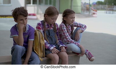 Back to School - Three classmates sitting outdoors in the...