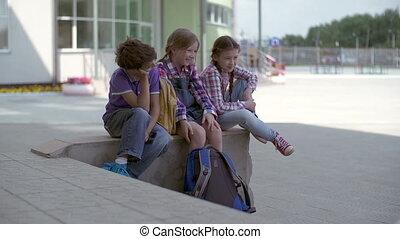After Class - Three schoolchildren taking rest after class...