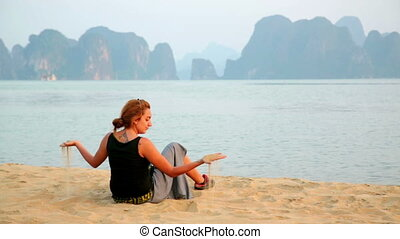 Tourist girl at beach, limestone view of halong bay, vietnam