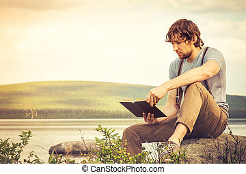 Young Man reading book outdoor with lake on background...