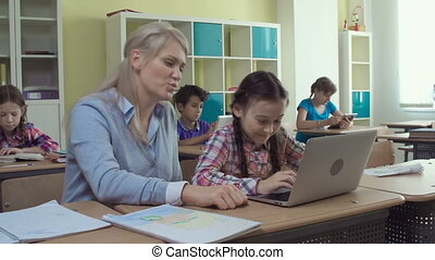 Information Technology in Education - Teacher helping pupil...