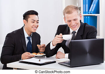 Two businessmen eating lunch and looking on laptop