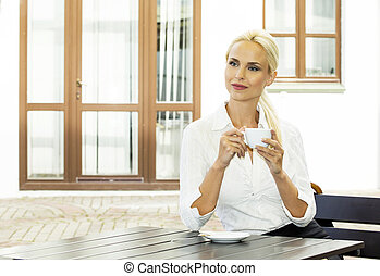 young woman drinking coffee - young woman in a cafe with a...