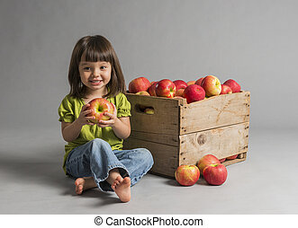 Child with crate of apples beside her.