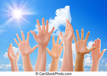 Raised up hands of many people on background of blue sunny...