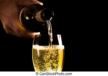 Pouring a white wine into a glass - Hand of a man pouring a...