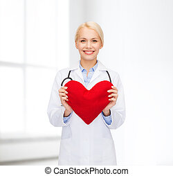 smiling female doctor with heart and stethoscope -...
