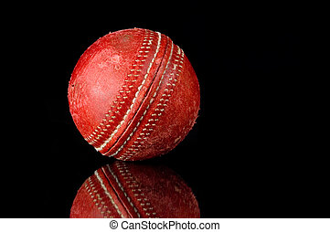 Red Cricket ball on black background - Red, scuffed Cricket...