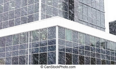 Exterior of new office building in snowfall - Facade view at...