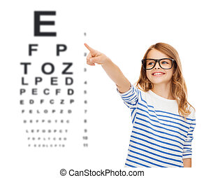 cute little girl in eyeglasses pointing in the air -...
