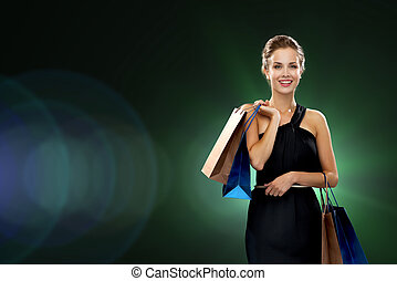 smiling woman in dress with shopping bags - shopping, sale,...