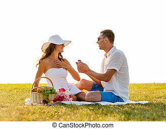 smiling couple with small red gift box on picnic - love,...