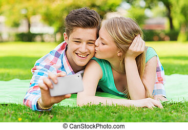 smiling couple making selfie and kissing in park - vacation,...