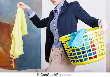 Businesswoman collecting dirty clothes before going to work