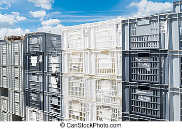 empty plastic crates - piled up empty plastic crates on an...