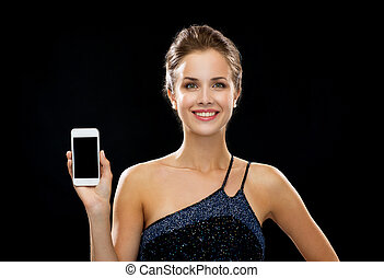 smiling woman in evening dress holding smartphone -...