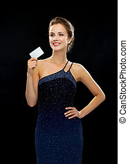 smiling woman in evening dress holding credit card - wealth,...