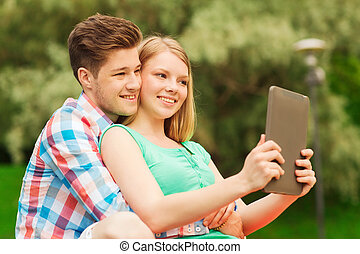 smiling couple with tablet pc making selfie - vacation,...