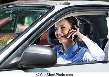 Happy woman driving car - Happy woman talks on phone during...
