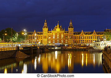 Night city view of Amsterdam canal and Centraal Station,...