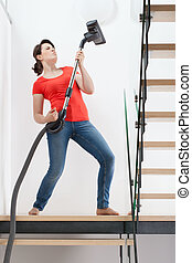 Girl having fun during vacuuming floor, vertical
