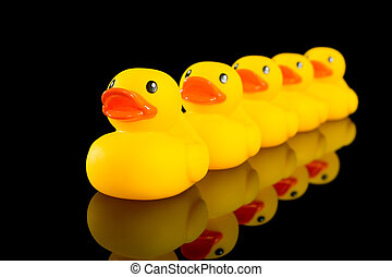 Ducks in a row - A row of yellow ducks on a black background...