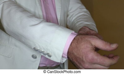 man adjusts his cufflinks - a man in a pink shirt adjusts...